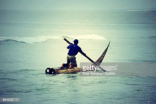 Rear View Of Man Rowing Wooden Raft In Sea