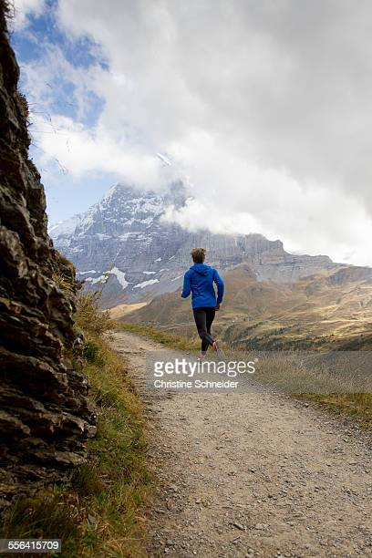 Rear view of man running along dirt track toward mount Eiger, Grindelwald, Switzerland