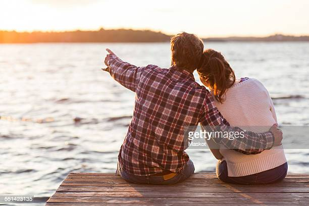 Rear view of man showing something to woman while sitting on pier against sea at sunset