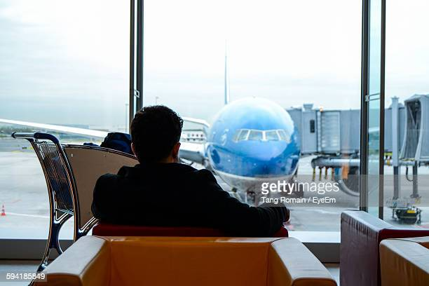 Rear View Of Man Sitting At Airport Waiting Area