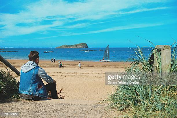 Rear View Of Man Sitting At Beach Against Sky