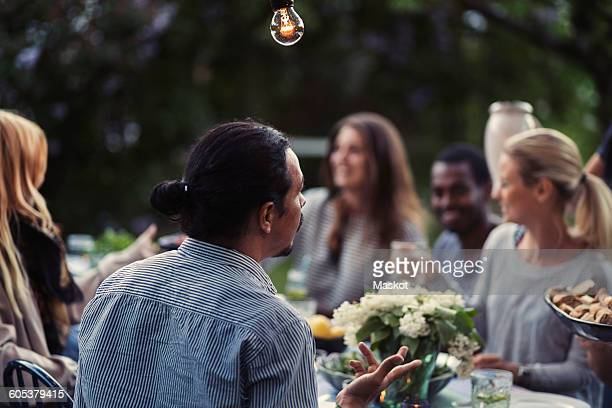 Rear view of man sitting at dining table with friends at outdoor dinner party
