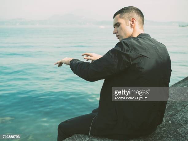 Rear View Of Man Sitting By Sea