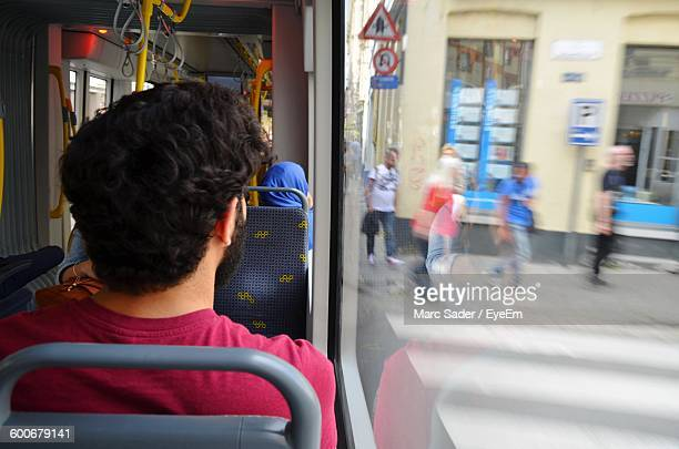 Rear View Of Man Sitting In Bus