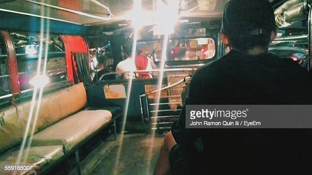 Rear View Of Man Sitting In Illuminated Jeepney At Night