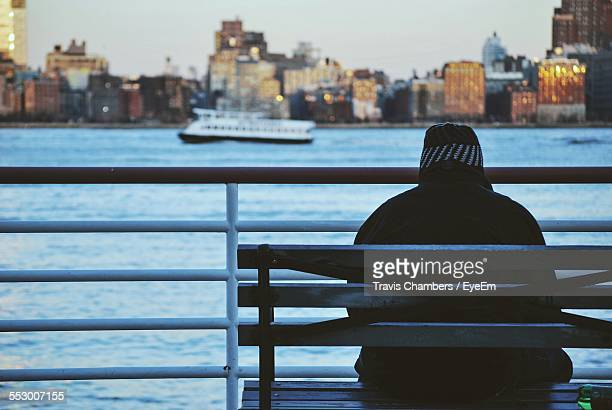 Rear View Of Man Sitting On Bench And Watching City
