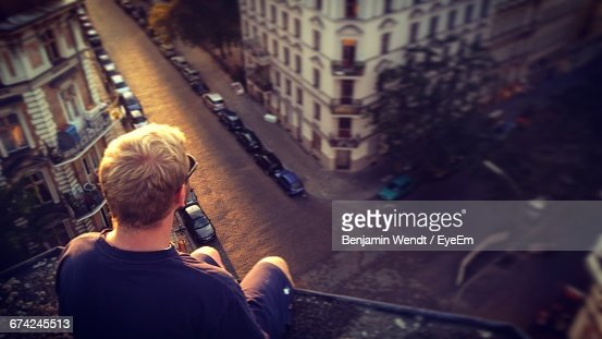 Rear View Of Man Sitting On Building Terrace