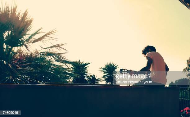 Rear View Of Man Sitting On Surrounding Wall Playing Guitar Against Sky