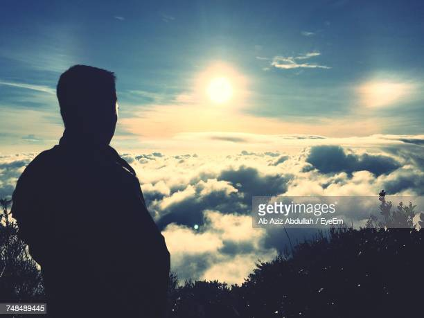 Rear View Of Man Standing Against Cloudy Sky On Sunny Day