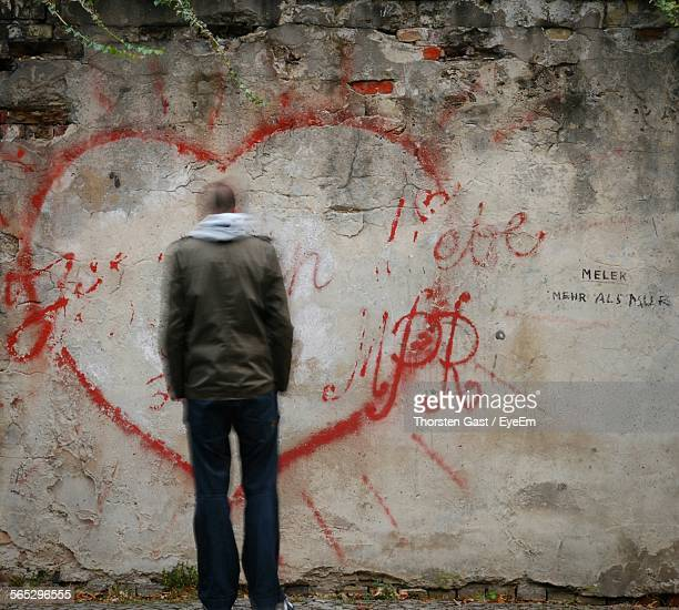 Rear View Of Man Standing Against Heart Shaped Drawing On Wall