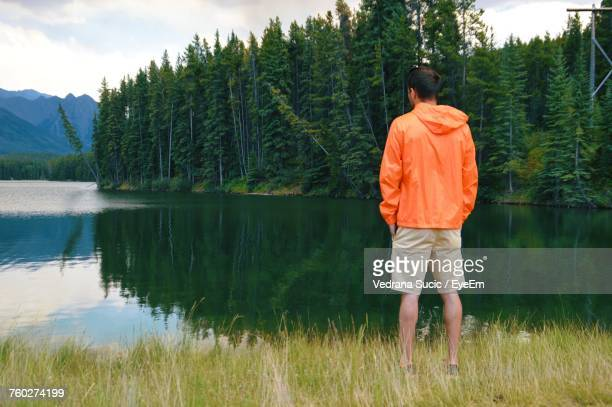 Rear View Of Man Standing Against Lake With Reflection