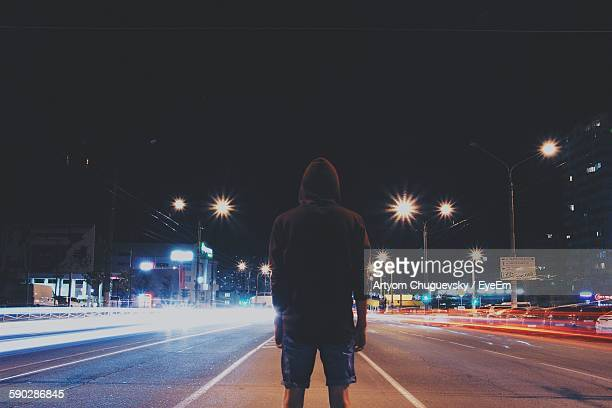 Rear View Of Man Standing Amidst Light Trails On Street At Night