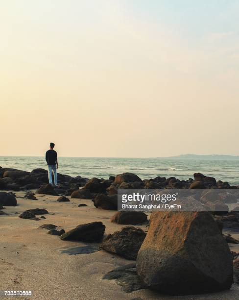 Rear View Of Man Standing At Rocky Beach Against Sky During Sunset