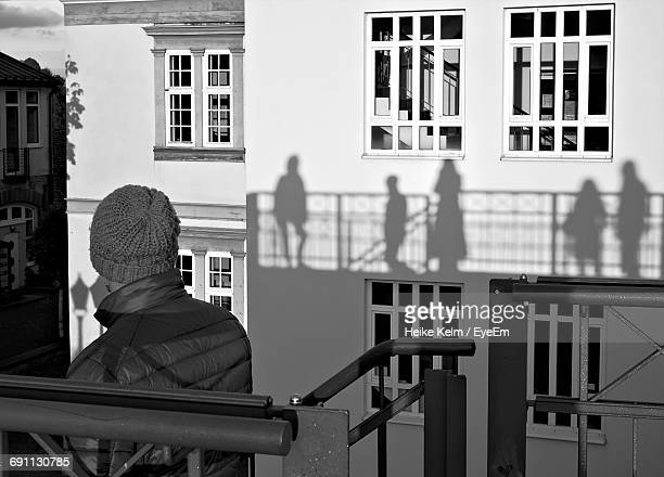 Rear View Of Man Standing At Steps By Shadows On Building In City