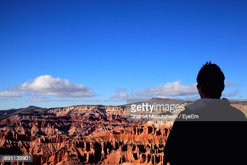 Rear View Of Man Standing By Cedar Breaks National Monument Against Sky