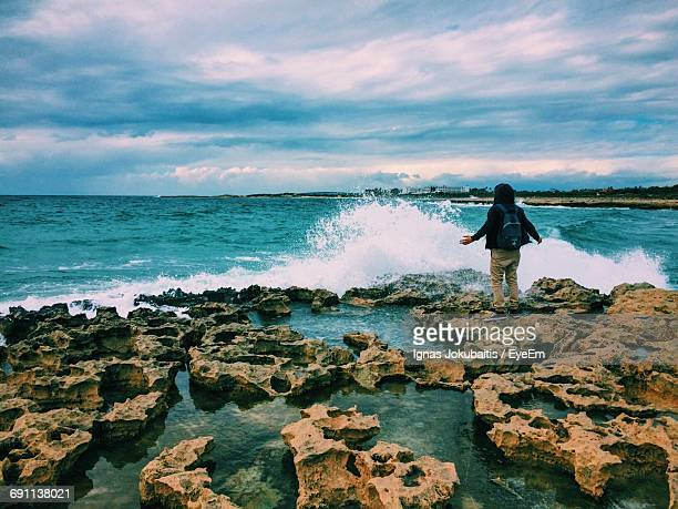 Rear View Of Man Standing By Waves Splashing On Rocks Against Cloudy Sky