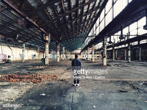 Rear view of man standing in abandoned factory