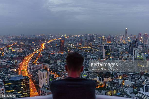 Rear View Of Man Standing In Balcony Against Illuminated Cityscape