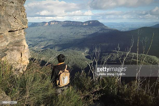 Rear View Of Man Standing In Grass Looking At Lush Green Landscape In Katoomba