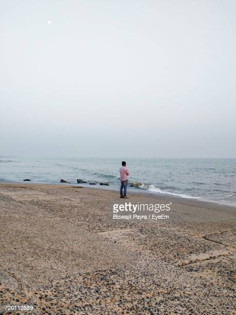 Rear View Of Man Standing On Concrete Shore Looking At Horizon