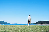 Rear View Of Man Standing On Grass Against Sky