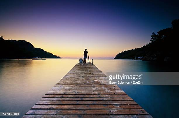 Rear View Of Man Standing On Pier At Lake Against Clear Sky During Sunset