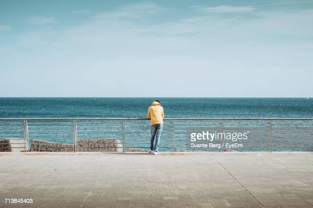 Rear View Of Man Standing On Seashore