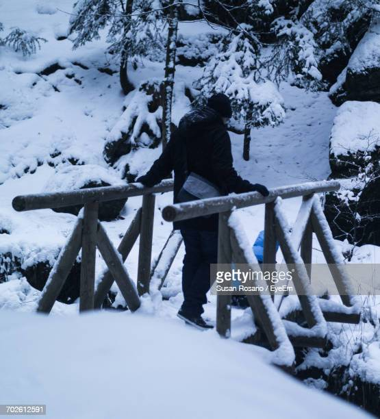 Rear View Of Man Standing On Snow Covered Footbridge During Winter