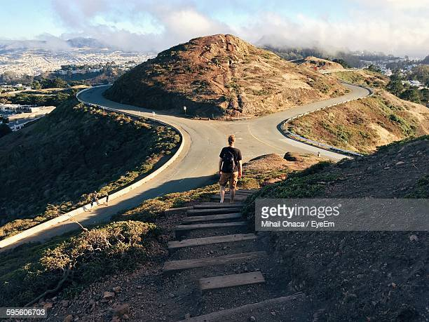 Rear View Of Man Standing On Steps In Front Of Mountain Roads