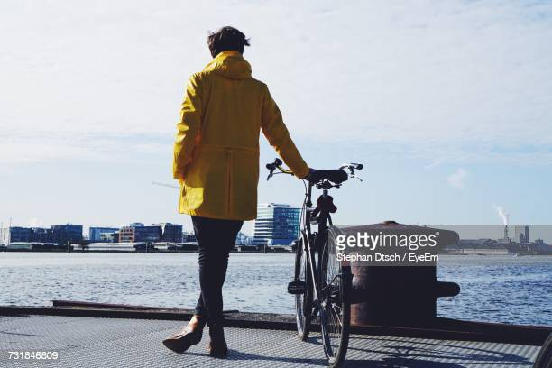 Rear View Of Man Standing With Bicycle By River