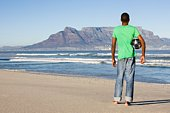 Rear view of man standing with football, Table Mountain beach