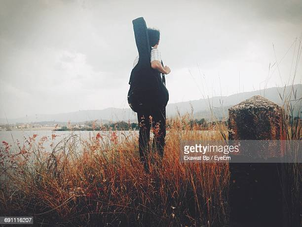 Rear View Of Man Standing With Guitar On Grassy Field Against Sky