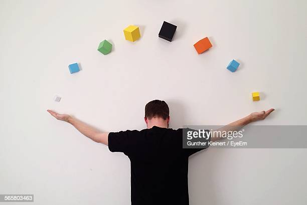 Rear View Of Man Stretching Arms On Wall With Colorful Cubes