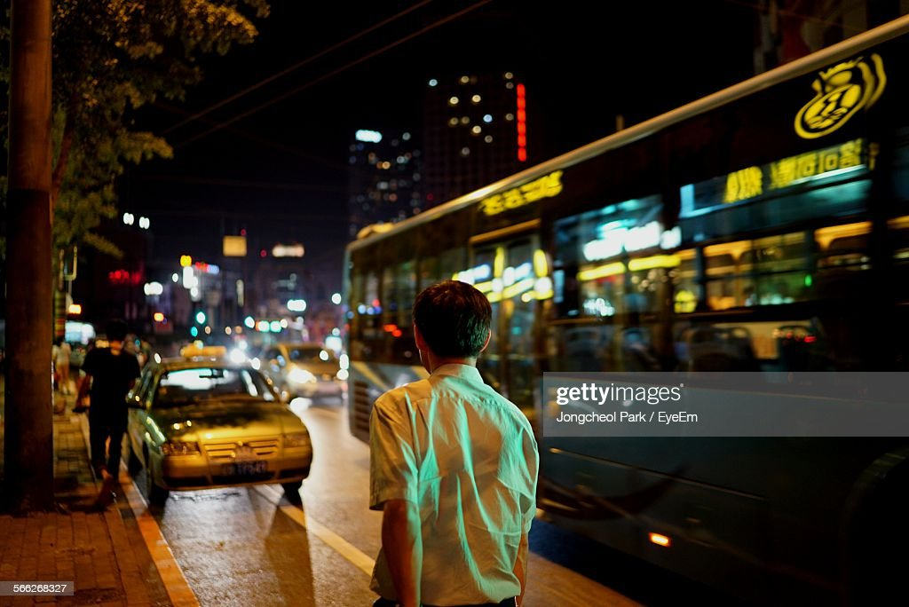 Rear View Of Man Walking By Bus On Street At Night