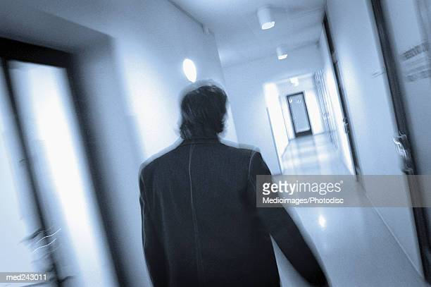 Rear view of man walking down hallway, defocused, tilt