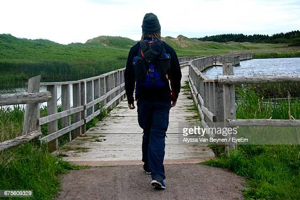 Rear View Of Man Walking On Footbridge Over River By Green Hills
