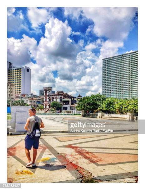 Rear View Of Man Walking On Footpath In City Against Cloudy Sky