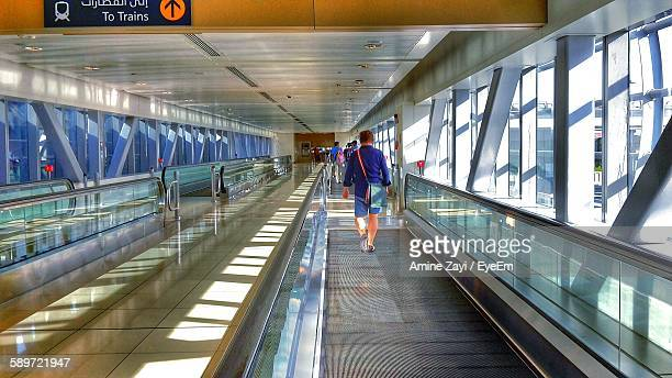 Rear View Of Man Walking On Moving Walkway At Railroad Station