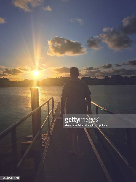 Rear View Of Man Walking On Pier Over River Against Cloudy Sky During Sunset