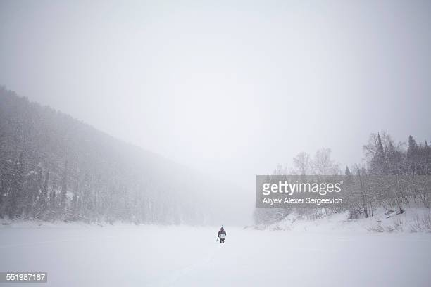 Rear view of man walking through snow covered valley, Sarsy Village, Sverdlovsk Oblast, Russia