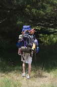 Rear view of man walking with backpack and gear