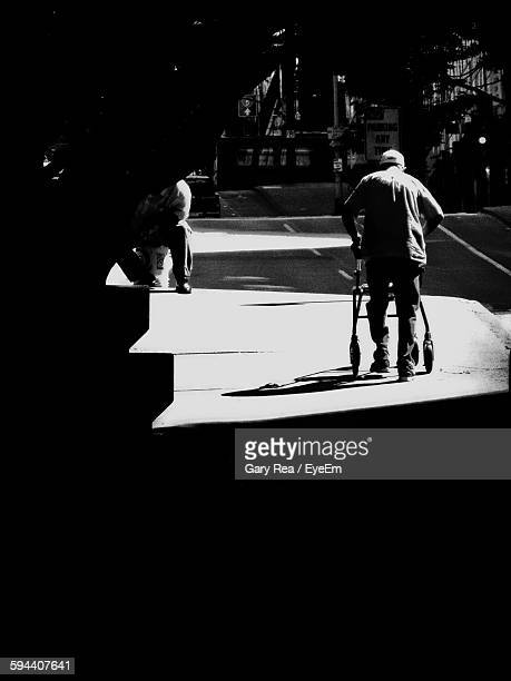 Rear View Of Man Walking With Rollator On Street