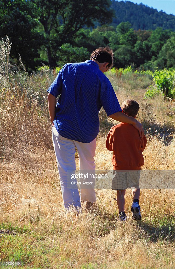 Rear view of man walking with son : Stock Photo