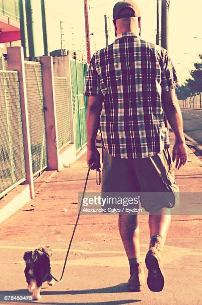 Rear View Of Man Walking With Yorkshire Terrier On Sidewalk