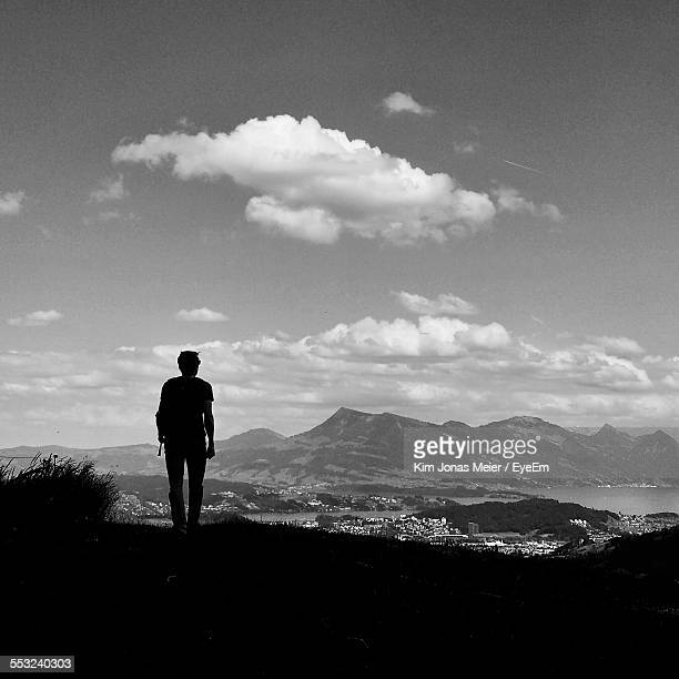 Rear View Of Man Watching Mountains Against Sky