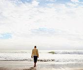 Rear view of man watching ocean
