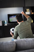 Rear view of man watching sports on tv, Jersey City, New Jersey, USA