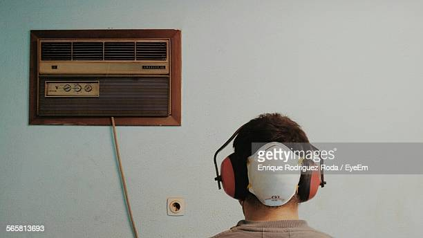 Rear View Of Man Wearing Ear Muff Against Wall At Home