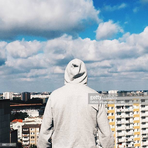 Rear View Of Man Wearing Hooded Shirt Standing By Buildings Against Cloudy Sky
