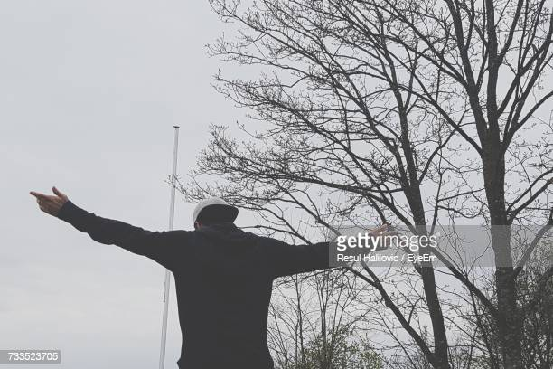 Rear View Of Man With Arms Outstretched Standing By Bare Trees Against Sky